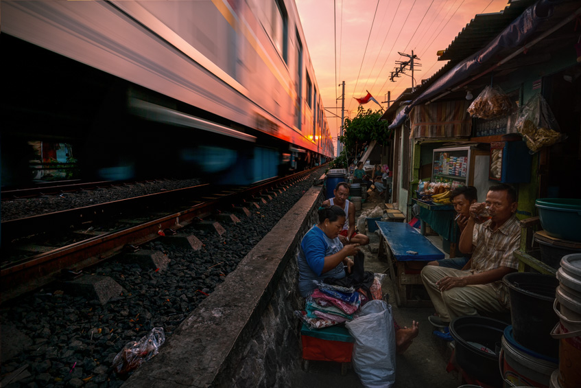 people sitting at their slum houses while a train rushes close by