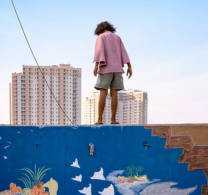 Girs standing on a wall and Looking Beyond the Slum