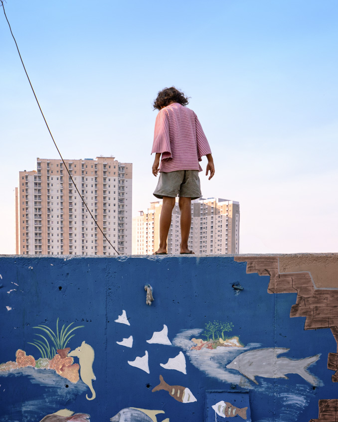 slum girl standing on the wall