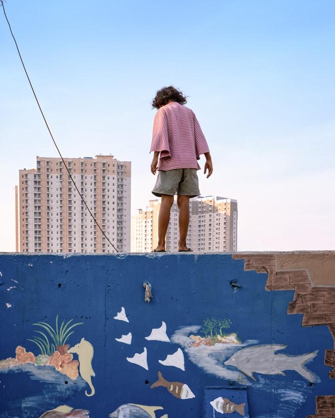 slum girl standing on the wall
