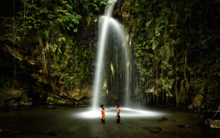 two kids under the waterfall